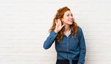 Redhead Woman Over White Brick Wall Listening To Something By Putting Hand On The Ear