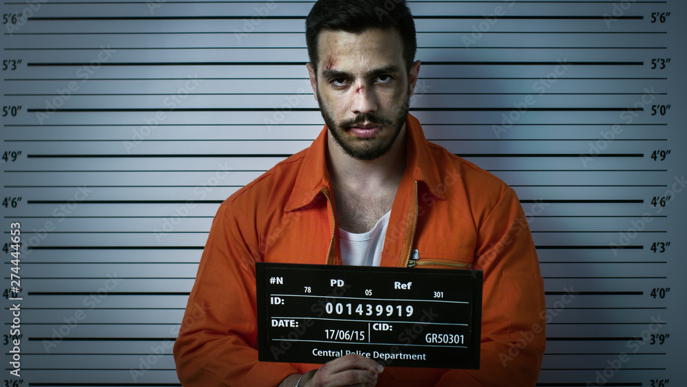 Fototapeta In a Police Station Arrested Man Getting Front-View Mug Shot. He's Wearing Prisoner Orange Jumpsuit and Holds Placard. Height Chart in the Background. Shot with Dark Cold Lights, Vignette Filter.
