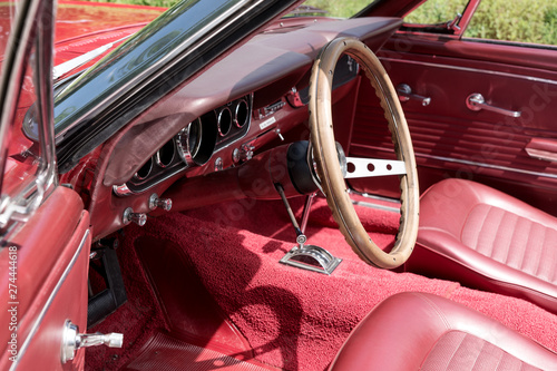 Foto op Plexiglas Cubaanse oldtimers Interior view with instruments and wooden steering wheel of an old red cabriolet