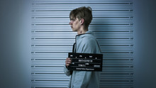 In A Police Station Arrested Drug Addict Teenage Posing For A Side View Mugshot. He Is Heavily Bruised. Height Chart In The Background.