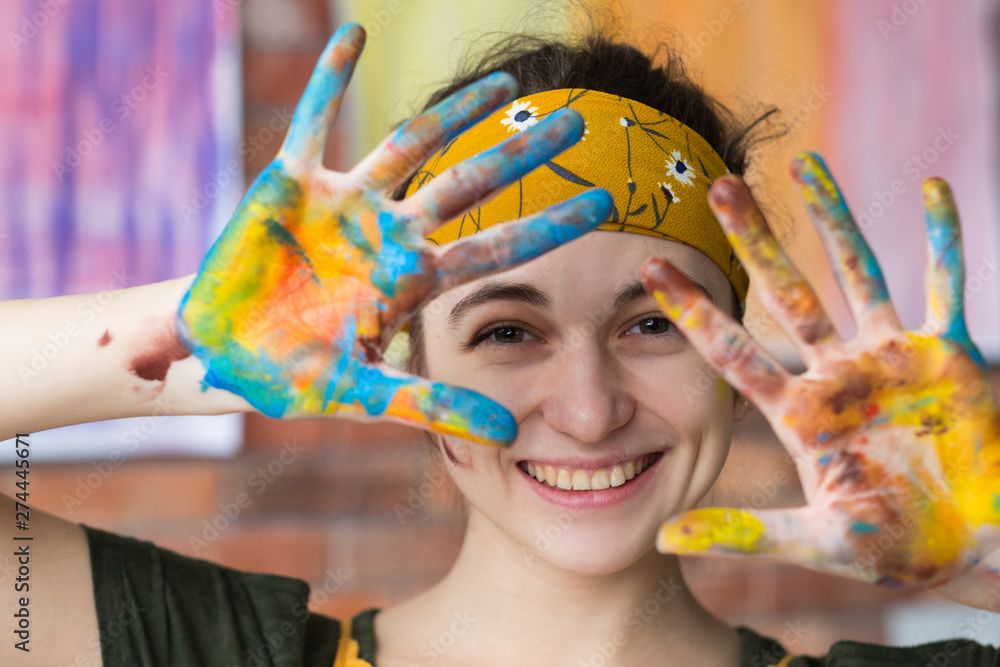 Fototapeta Art therapy. Closeup portrait of young female artist having fun in studio, smiling, showing hands dirty with paint.