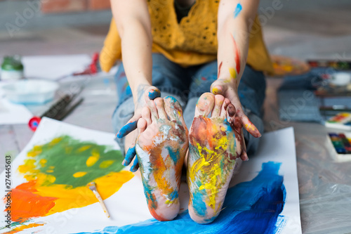 Art therapy. Cropped shot of artist sitting on floor, showing feet and hands dirty with multicolor paint. Blur background.