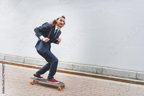 happy and handsome businessman riding on skateboard at street