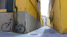 A View Of A Narrow Yellow Street Of Pisa