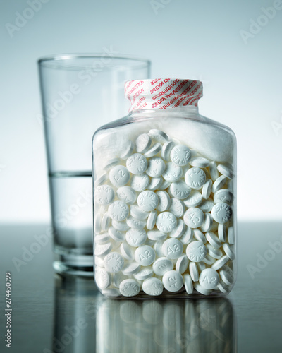 Safety sealed bottle of aspirin pills with glass of water Wallpaper Mural