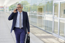 Mature Businessman Talking On Cellphone Outside Modern Office Building