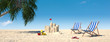 Sandcastle and loungers on the beach with palm tree