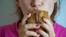 Young Woman Eating Fast Food Sandwich With Pleasure In Cafe