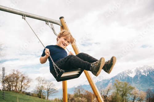 Kid boy having fun on swing in swiss alps, playground with beautiful view