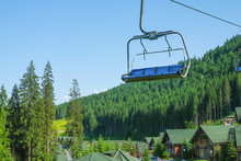 Scenic Lift Rides In The Carpathian Mountains In Ukraine. In The Valley There Are Wooden Houses With Green Roofs. Empty Chair Of The Cable Car.