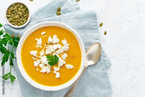 Fotografie, Obraz  Pumpkin cream soup with feta cheese, autumn homemade food, white background, top
