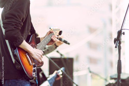 Close-up of the hands of a young guitarist who plays a solo on an electric guitar during a rock open-air concert on stage with his musical band. Copy space on the right side for designers. - 274476495