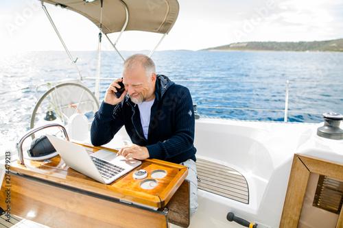 Obraz na płótnie Digitaler Nomade arbeitet am Laptop lachend und telefonierend auf einem Segelboo