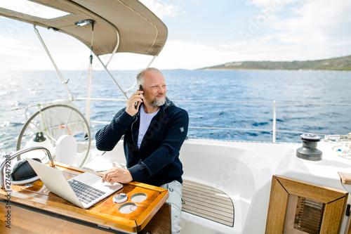 Cuadros en Lienzo  Digitaler Nomade mit Laptop telefoniert mit Blick in die Ferne auf einem Segelbo