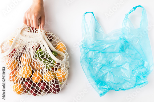 Fotografie, Obraz  Top view of mesh shopping bag with organic eco fruits isolated on white background