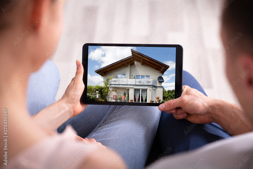 Fototapety, obrazy: Couple Looking At House On Tablet