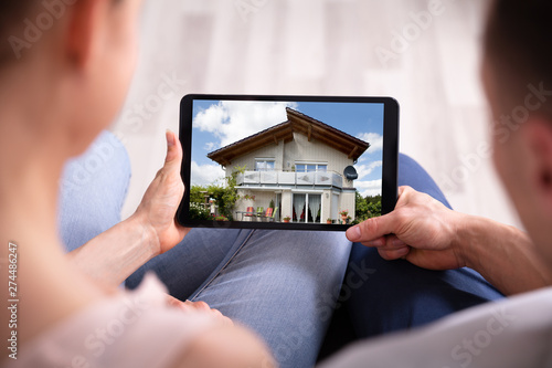 Fotografía  Couple Looking At House On Tablet