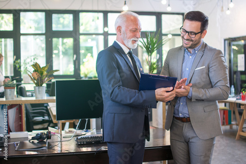Fototapeta Senior businessman in formal wear discussing data from clipboard with younger male colleague while standing together in office. obraz