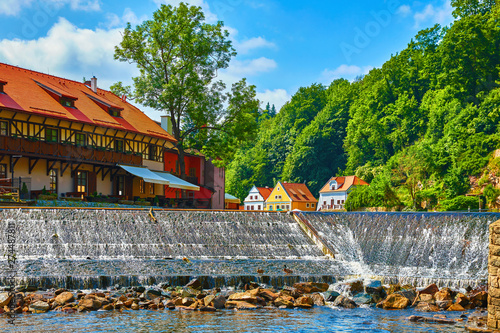 Cesky Krumlov (Czech Krumlov), Czech Republic. Antique town on river Vltava. Picturesque landscape. Cascade dam with stones. Colourful houses on bank among green trees. Sunny summer day with blue sky.