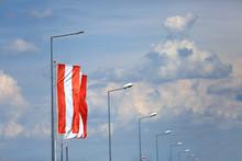 Flaga Na Maszcie I Latarnie Uliczne Na Tle Zachmurzonego Nieba.