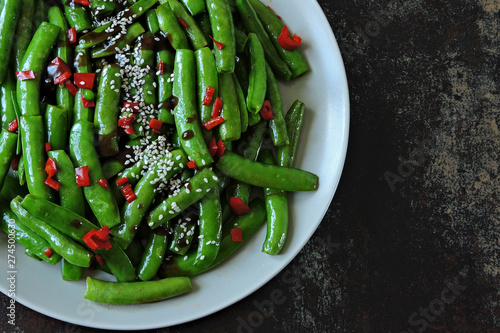 Green pea pods with chili pepper and sesame. Asparagus beans on a plate in the Chinese style. Vegan food. Healthy lunch. Diet food.