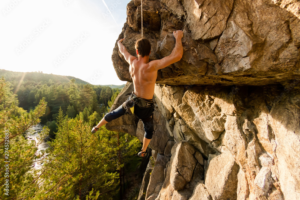 Fototapety, obrazy: Climber Extreme climbs a rock on a rope with the top insurance, overlooking the forest