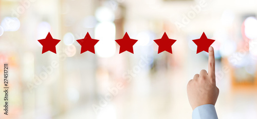 Cuadros en Lienzo Man hand pointing red five star over blur background, customer excellent rating