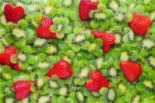 Top View Of Funny Creative Concept Sliced Kiwi Flower Shape And Strawberry Heart Shape Like Background