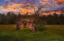 Old Abandoned Broken Barn At The Edge Of The Forest With Tall Green Grass And Wild Flowers At Sunset. Styled Stock Photo In Romania. Hidden Gem Travel Destination In The Countryside.