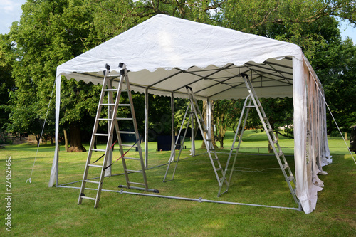Obraz event tent set up  with ladders on the lawn in a park for a summer party or wedding - fototapety do salonu