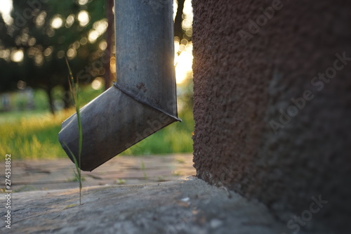 Drainpipe with a beautiful sunlight on the background of the spring garden Canvas-taulu