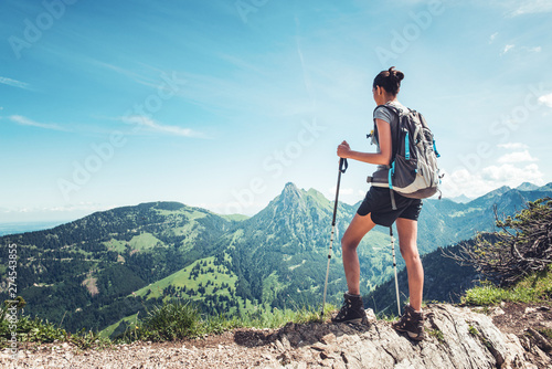 Obraz Fit female hiker standing on a mountain ridge - fototapety do salonu