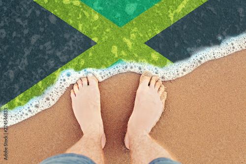 Feet on the sunny sandy beach with flag Jamaica  Top View on