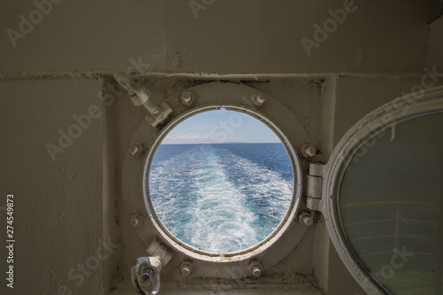 Fototapeta  metal porthole scuttle on a fast ferry with the view of the backwash and waterwa