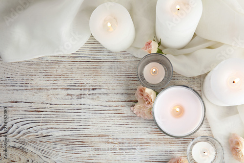 Recess Fitting Relaxation Flat lay composition with burning aromatic candles and roses on wooden table. Space for text