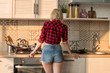 Beautiful sexy girl standing at the stove in the kitchen.