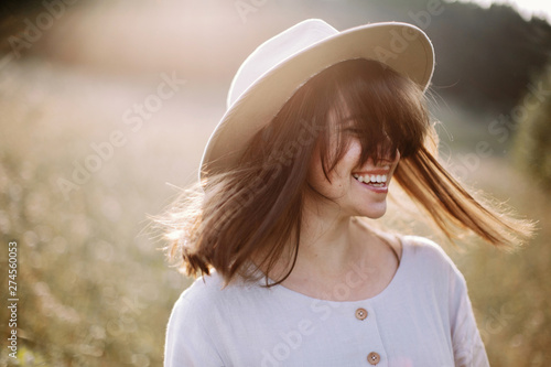 Fotografía  Stylish girl in rustic dress smiling and waving hair in sunny meadow in mountains