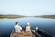 Grandfather With Adult Son Enjoying Beer, Sitting Together On The Pier While Fishing On The Lake Early In The Morning. Wide Landscape View