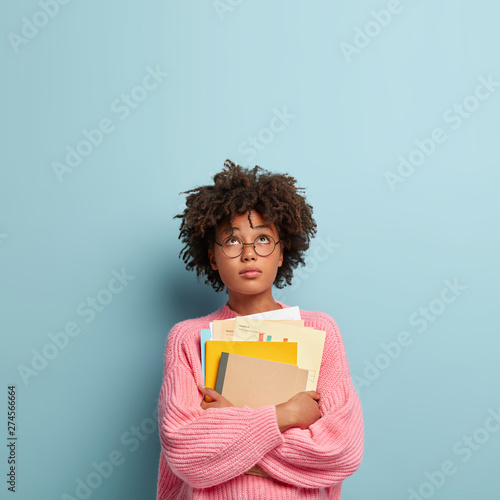 Fotomural  Hard working college student focused up, carries papers, textbook and notepad, wears oversized pink jumper, contemplates about finishing studying year, notices something above head