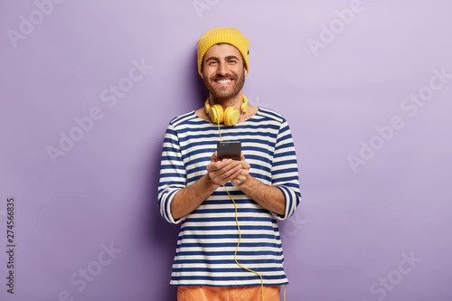 Waist up shof of glad attractive hipster wears stereo headphones and holds modern cell phone, listens audio track and checks notification, dressed in striped sailor jumper, yellow headgear, smiles - 274566835