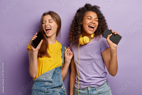 Obraz Optimistic pleased mixed race women sing favourite song in smart phones, have fun and enjoy music, keep eyes shut, move actively, isolated on purple background. People, free time and joy concept - fototapety do salonu