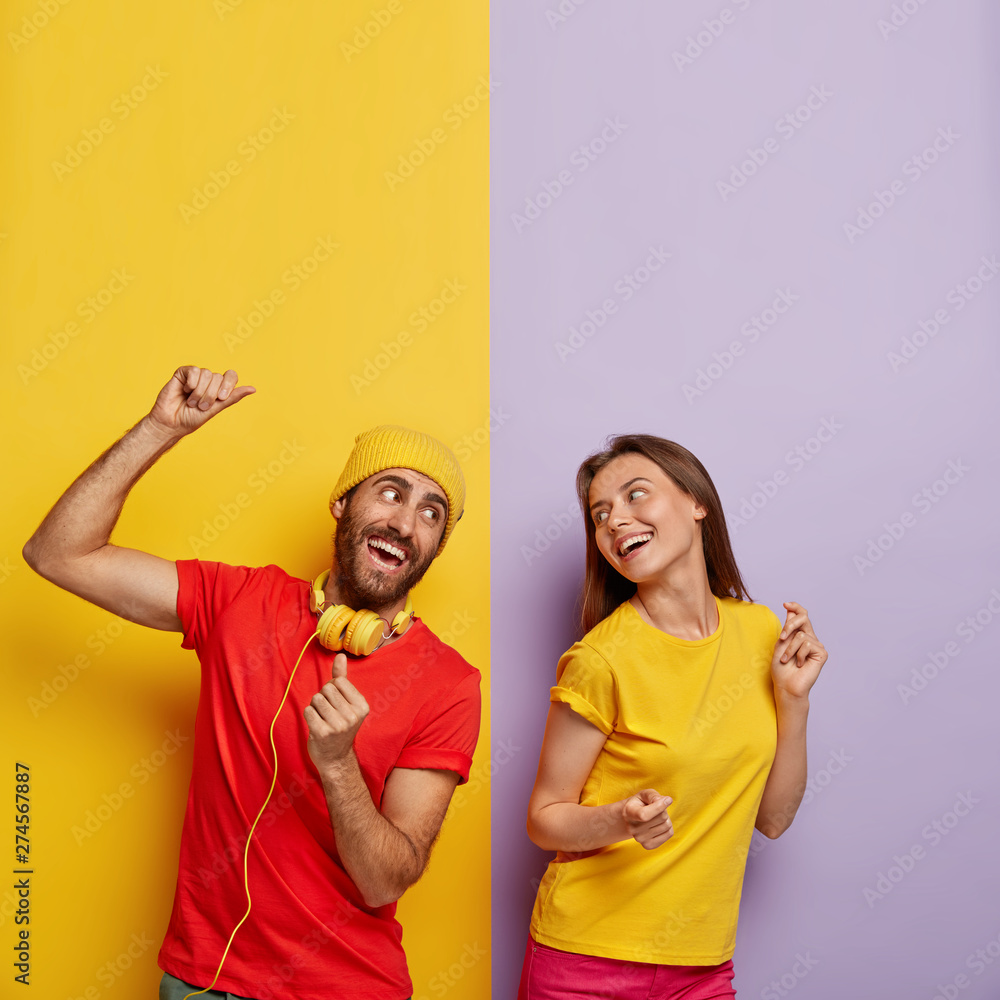 Fototapety, obrazy: Positive couple listen music together, dance and move actively, being in good mood. Cheerful man in red t shirt, headphones on neck, spends free time with girlfriend. People and entertainment concept