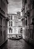 Fototapeta Uliczki - Venice in black and white, Italy. Old narrow street with lone gondola in distance.