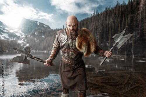 Viking with axes in hands standing at the lake Canvas Print