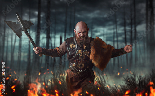 Fotografia Angry viking with axe, battle in forest