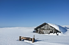 Old Abandoned And Ruined Village Hut With Chained Well. Everything Is Buried Under Snow Cover. Clear Sky, Bright Weather And Snow Desert Valley In The Background.