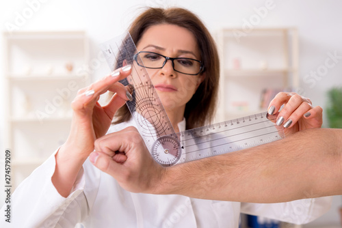 Female doctor checking patient's joint flexibility with goniometer Fotobehang
