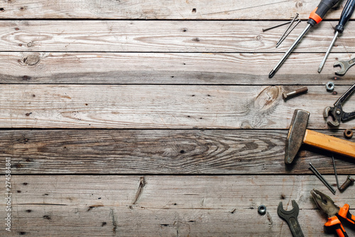 Obraz Flat lay composition with vintage carpentry tools on rough wooden background. Top view workbench with carpenter different tools. Woodworking, craftsmanship and handwork concept.  - fototapety do salonu