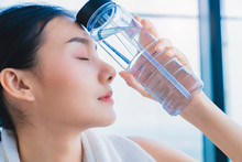 Asian Healthy Aport Woman Relaxing In Gym After Workout Hand Hold Pure Water Drink And White Towel