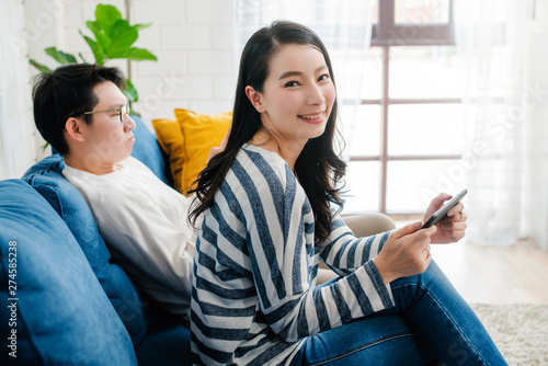 Fotografiet  happiness asian sweet couple enjoy game on smartphone together living room home